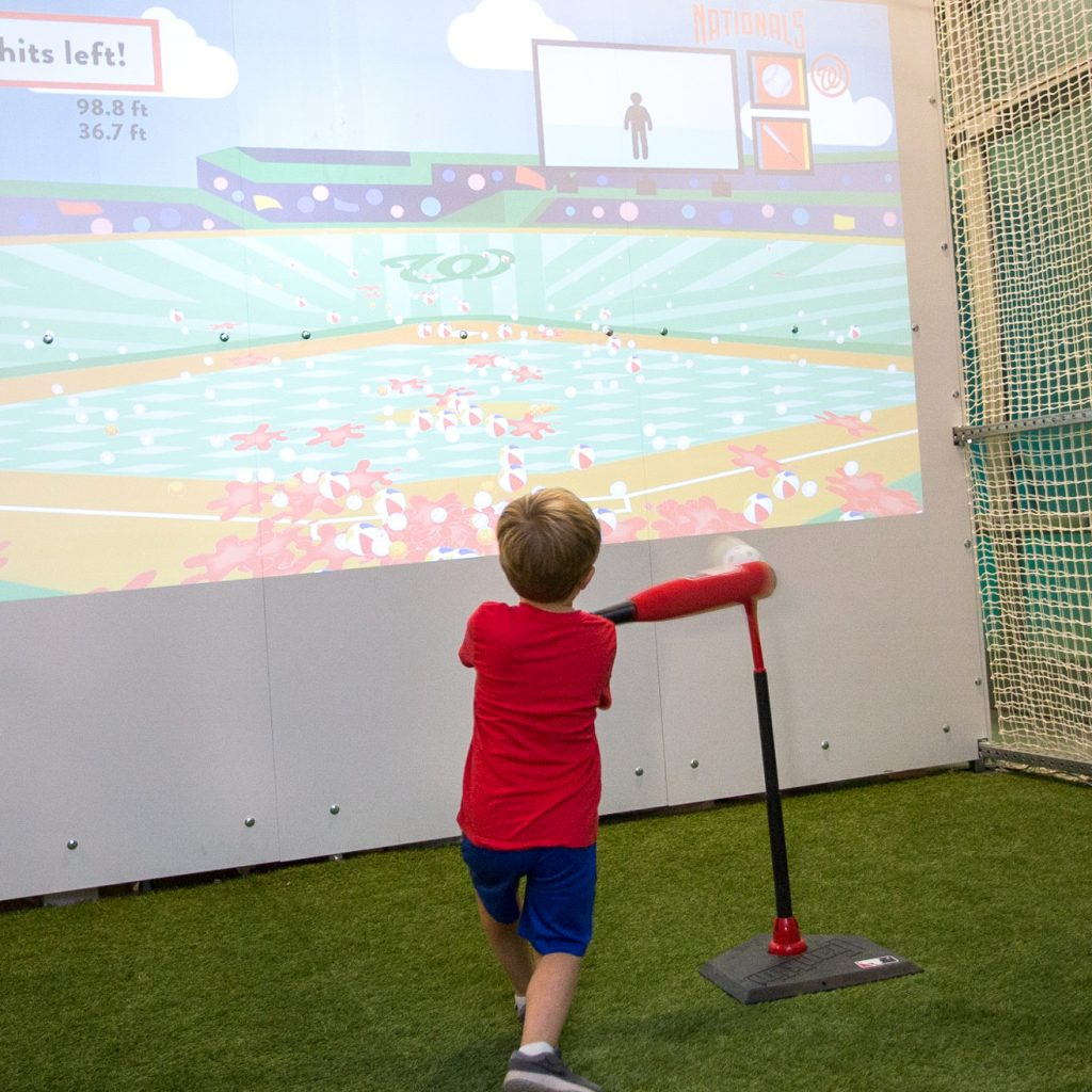 Little boy swinging a bat in the batting cage