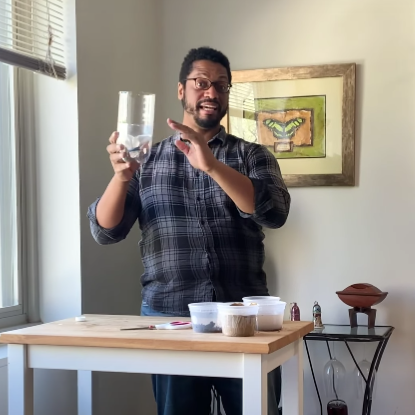 AJ stands behind a table, holding a clear plastic jug and smiling.