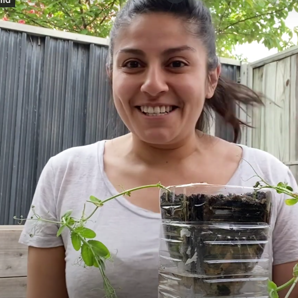 Christina smiles, holding her self-watering planter.