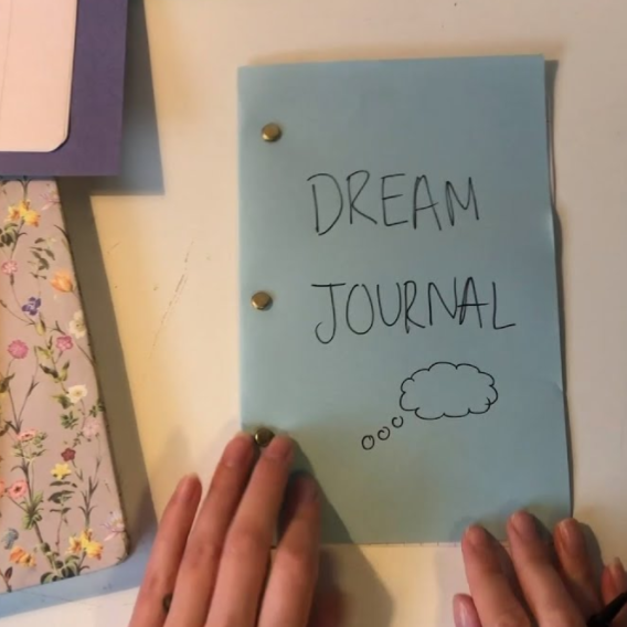 "Anna writes ""Dream Journal"" on her handmade notepad."